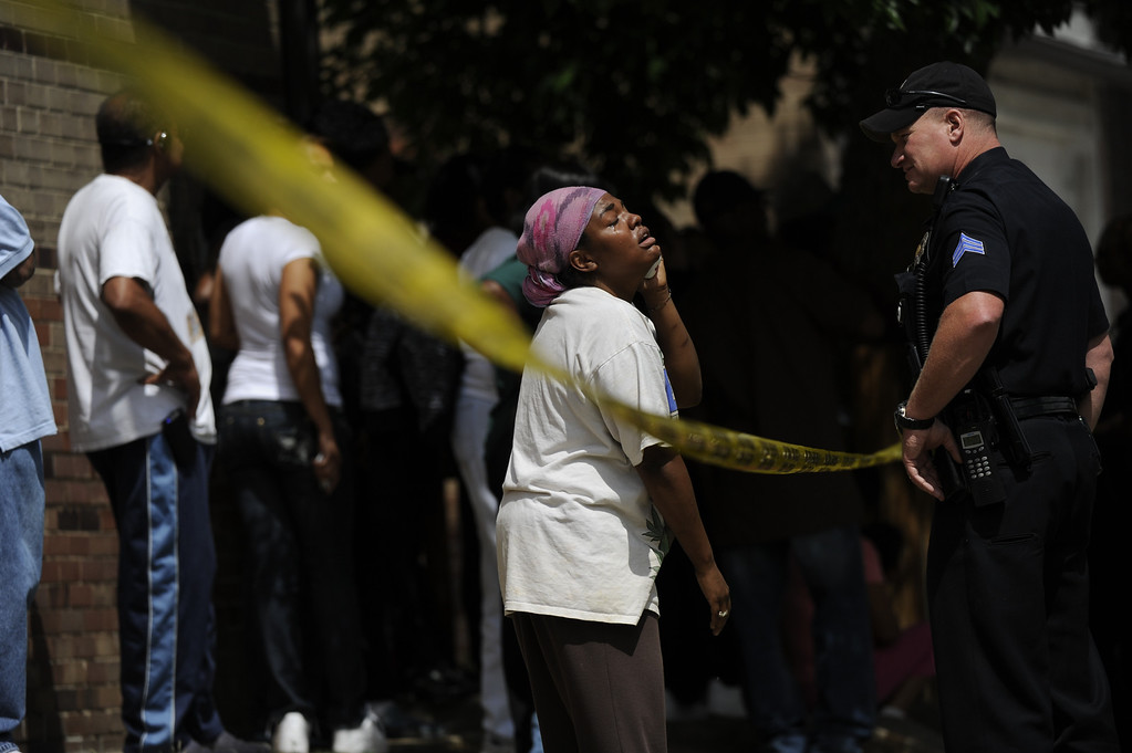 . A woman cries at the scene of a shooting in northeast Denver. Two people were killed and two were taken to a hospital after a shooting in northeast Denver on Friday, May 25, 2012. Shortly after 2:10 p.m., officers were called to East 33rd Avenue and York Street after a report of shots fired, according to the Denver Police Department. (Cyrus McCrimmon, The Denver Post)