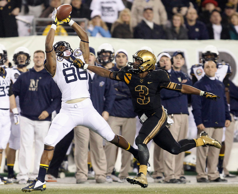 . Navy receiver Brandon Turner (86) catches a pass under pressure from Army defender Chris Carnegie (3) during the fourth quarter of the Army versus Navy NCAA football game in Philadelphia, Pennsylvania, December 8, 2012. REUTERS/Tim Shaffer