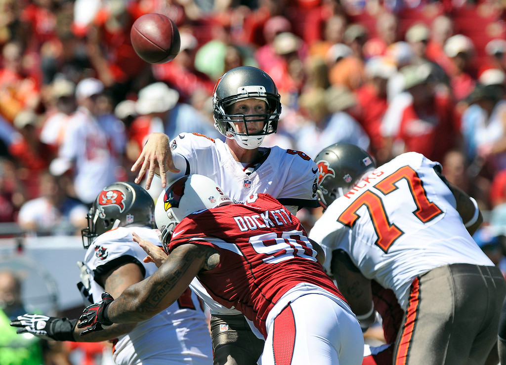 . Tampa Bay Buccaneers quarterback Mike Glennon (8) is hit by Arizona Cardinals defensive end Darnell Dockett (90) as he releases the ball during the first quarter of an NFL football game Sunday, Sept. 29, 2013, in Tampa, Fla. (AP Photo/Brian Blanco)
