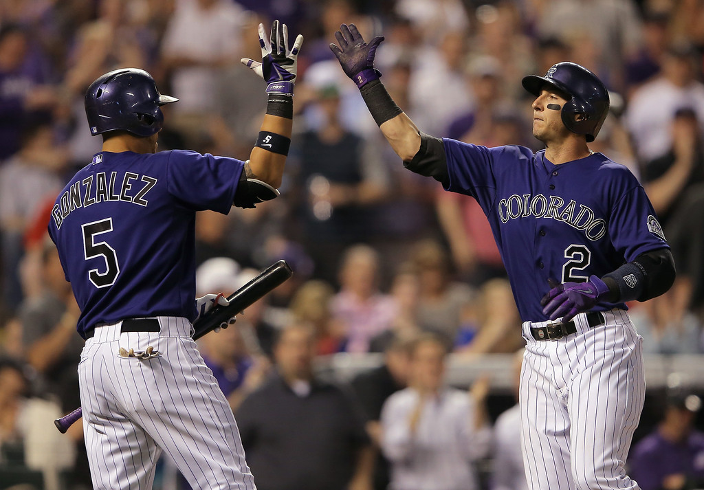 . Troy Tulowitzki #2 of the Colorado Rockies celebrates his two run home run off of starting pitcher Martin Perez #33 of the Texas Rangers with Carlos Gonzalez #5 of the Colorado Rockies to give the Rockies a 5-0 lead in the fifth inning during Interleague play at Coors Field on May 5, 2014 in Denver, Colorado.  (Photo by Doug Pensinger/Getty Images)