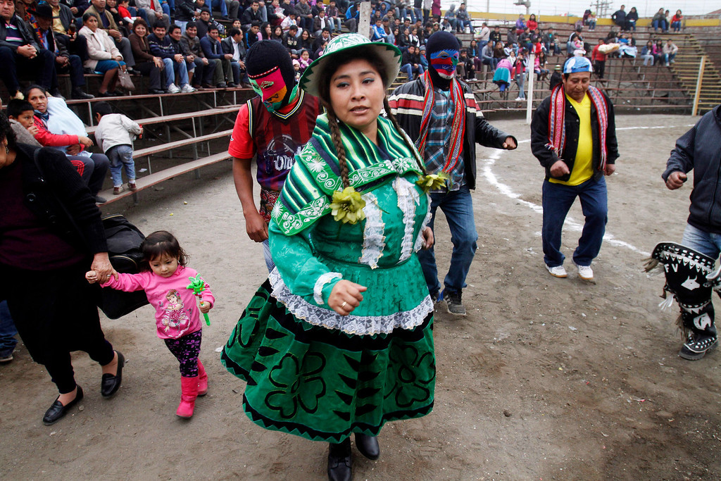 """. Participants of the Takanakuy fighting ritual dance before the start of the event in Lima, Peru. The Andean fight known as Takanakuy are preceding with traditional dancing and music. During the fights, women sing \""""huaylia\"""" music with lyrics in Quechua that include such lines as \""""Child, fear not when rivers of blood flow.\"""" (AP Photo/Karel Navarro)"""