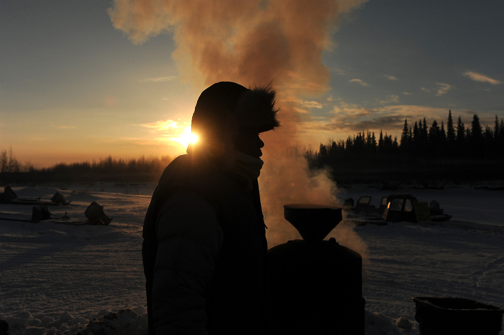 . Musher Newton Marshall gets hot water from the wood-fired heater at the Nikolai, Alaska, checkpoint during the Iditarod Trail Sled Dog Race at sunrise on Wednesday, March 5, 2014. The checkpoint provides hot water for all of the mushers. (AP Photo/Anchorage Daily News, Bob Hallinen)