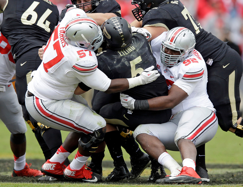 . Purdue quarterback Danny Etling, center, is sacked by Ohio State defensive lineman Adolphus Washington, right and Chase Farris during the second half of an NCAA college football game in West Lafayette, Ind., Saturday, Nov. 2, 2013. Ohio State defeated Purdue 56-0. (AP Photo/Michael Conroy)
