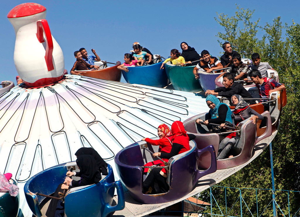 . Iraqis enjoy a ride at Amusement City fairgrounds during Eid al-Adha celebrations in Baghdad, Iraq, Monday, Oct. 29, 2012. Eid al-Adha is a Muslim holiday that commemorates the sacrifice by the Prophet Ibrahim, known to Christians and Jews as Abraham. It is a festive holiday where it is traditional for men, women and children to dress in new clothing and spend time with their families and outdoors. (AP Photo/Karim Kadim)