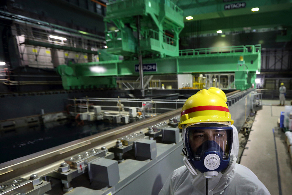 . A member of the media wearing a protective suit and a mask walks in front of a fuel handling machine on the spent fuel pool inside the building housing the Unit 4 reactor at the Fukushima Dai-ichi nuclear power plant in Okuma, Fukushima Prefecture, Japan, Thursday, Nov. 7, 2013.  (AP Photo/Tomohiro Ohsumi, Pool)