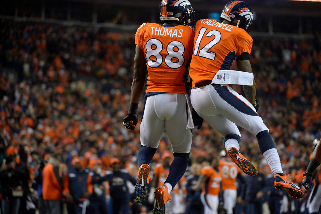 . Denver Broncos wide receiver Andre Caldwell (12) and wide receiver Demaryius Thomas (88) react to Caldwells first quarter touchdown. The Denver Broncos vs. the San Diego Chargers at Sports Authority Field at Mile High in Denver on December 12, 2013. (Photo by Joe Amon/The Denver Post)
