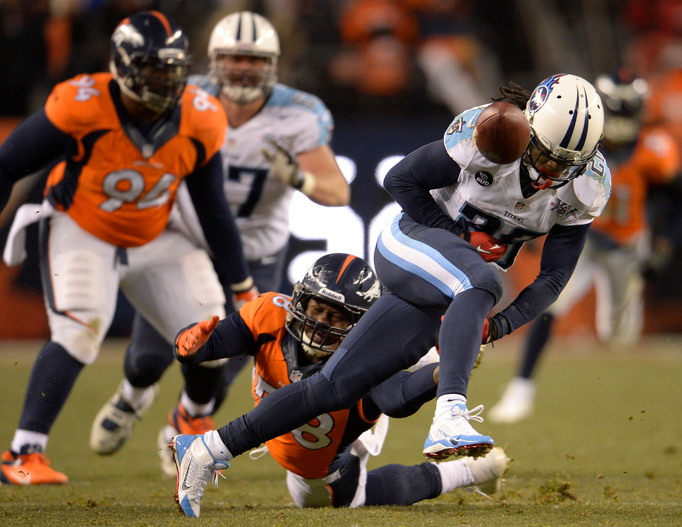 . Denver Broncos outside linebacker Von Miller (58) forces a fumble by Tennessee Titans running back Chris Johnson (28) during the fourth quarter. The Broncos recovered and went on to score a touchdown.   (Photo by Joe Amon/The Denver Post)