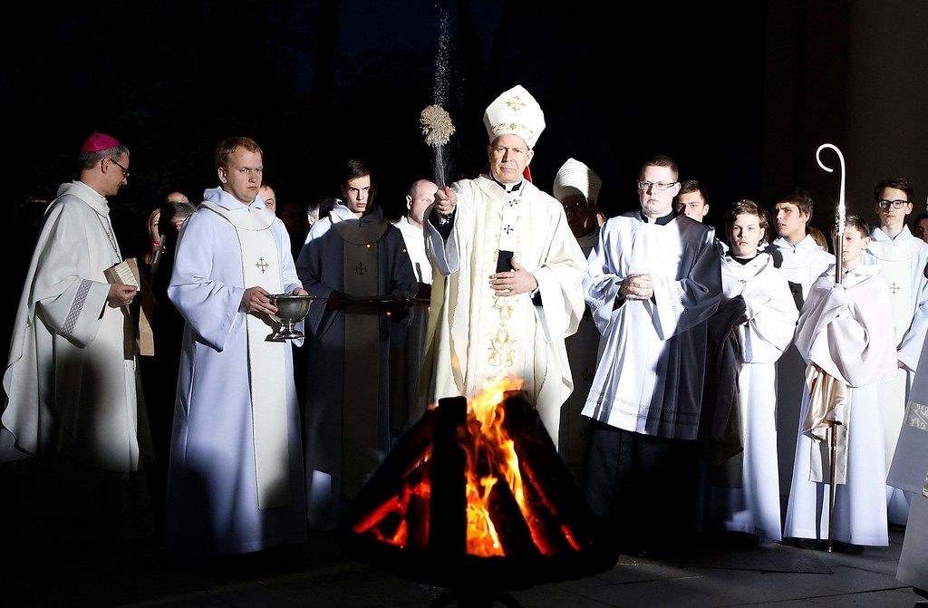 . Archbishop Gintaras Grusas perfoms the blessing at the Easter vigil mass in the Cathedral in Vilnius, Lithuania, Saturday April 19, 2014. (AP Photo/Mindaugas Kulbis)