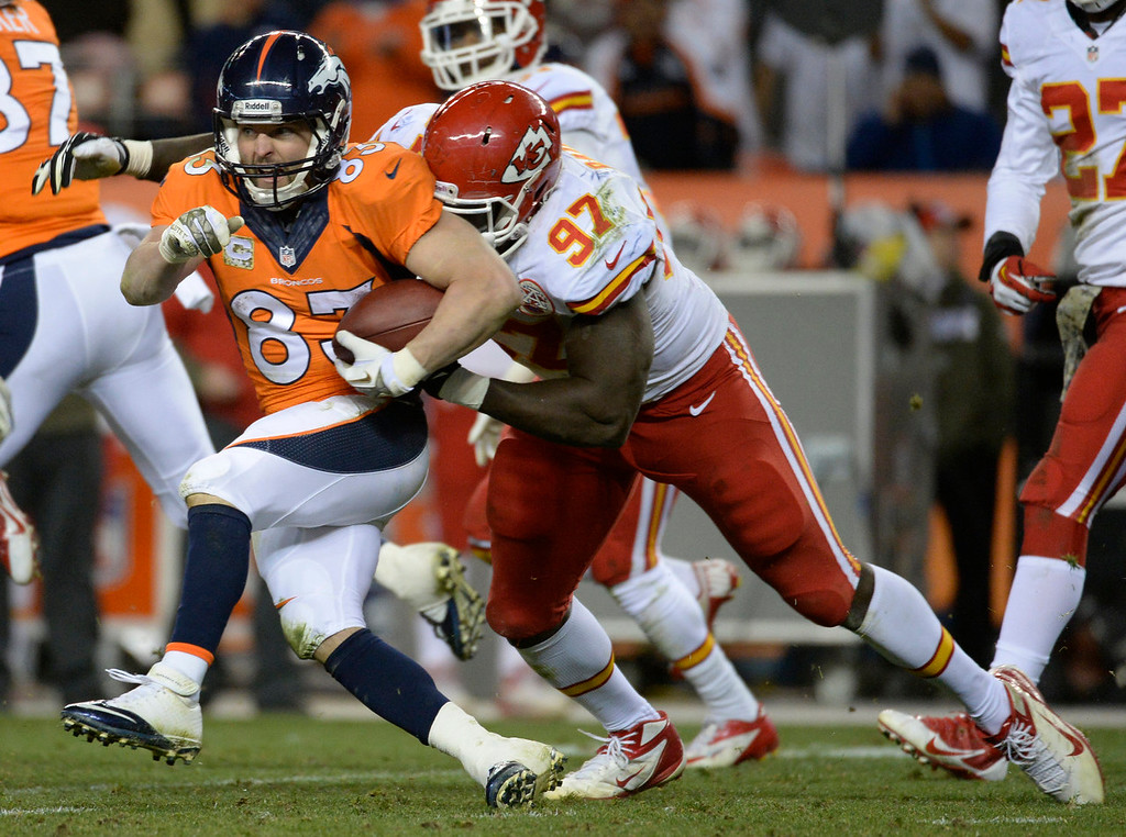 . Denver Broncos wide receiver Wes Welker (83) runs after a catch as Kansas City Chiefs defensive end Allen Bailey (97)  comes to hit him.  Welker was hurt on the play. The Denver Broncos vs. the Kansas City Chiefs at Sports Authority Field at Mile High in Denver on November 17, 2013. (Photo by Tim Rasmussen/The Denver Post)