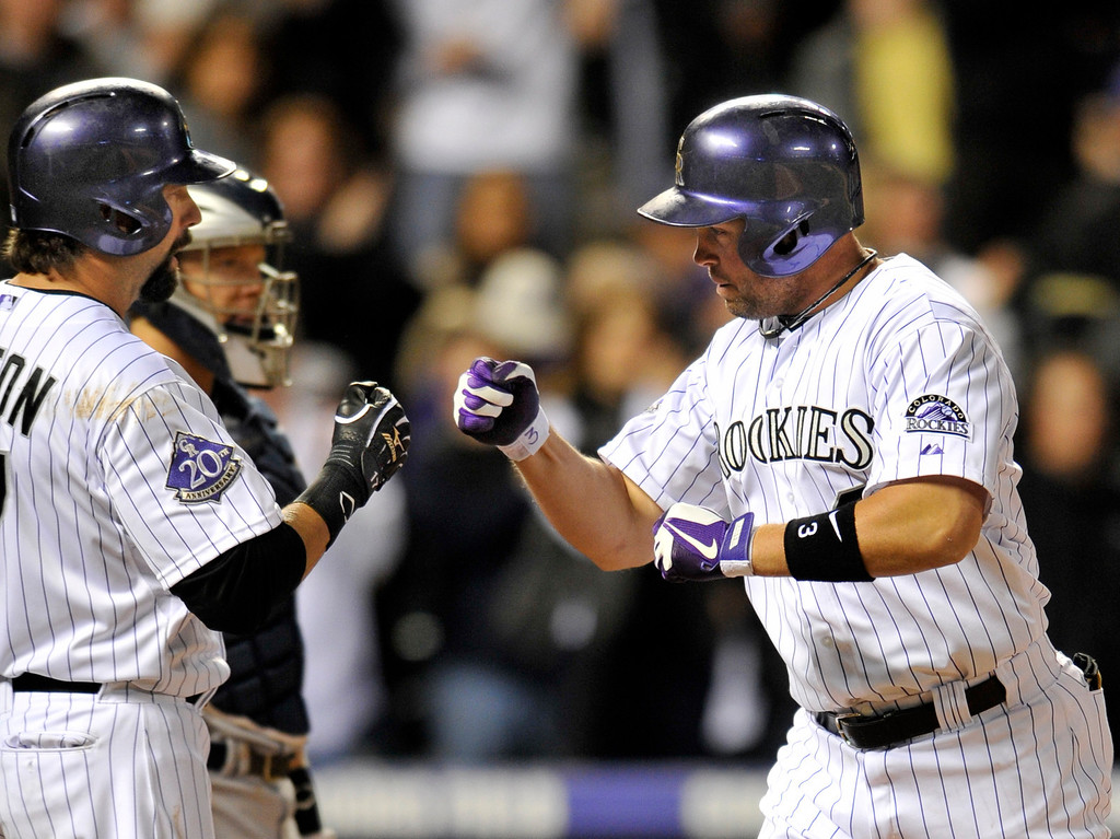 . Colorado Rockies\' Michael Cuddyer celebrates a two-run home run hit off San Diego Padres relief pitcher Andrew Cashner with teammate Todd Helton during the seventh inning of a baseball game on Saturday, April 6, 2013, in Denver. (AP Photo/Jack Dempsey)