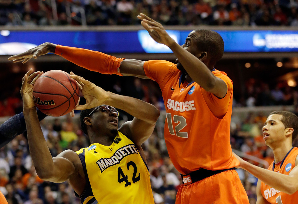 . Chris Otule #42 of the Marquette Golden Eagles makes draws contact against Baye Keita #12 of the Syracuse Orange during the East Regional Round Final of the 2013 NCAA Men\'s Basketball Tournament at Verizon Center on March 30, 2013 in Washington, DC.  (Photo by Win McNamee/Getty Images)