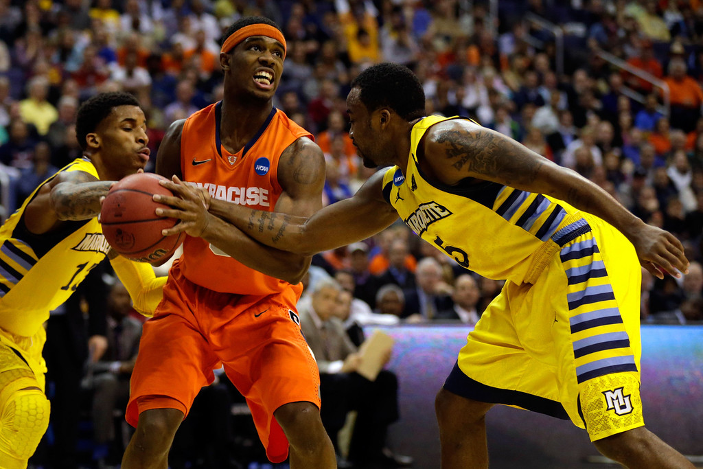 . WASHINGTON, DC - MARCH 30:  C.J. Fair #5 of the Syracuse Orange handles the ball against Junior Cadougan #5 and Vander Blue #13 of the Marquette Golden Eagles during the East Regional Round Final of the 2013 NCAA Men\'s Basketball Tournament at Verizon Center on March 30, 2013 in Washington, DC.  (Photo by Win McNamee/Getty Images)