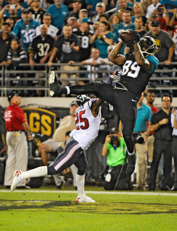 . Jacksonville Jaguars tight end Marcedes Lewis (89) catches a pass for a 1-yard touchdown in front of Houston Texans cornerback Kareem Jackson (25) during the first half of an NFL football game in Jacksonville, Fla., Thursday, Dec. 5, 2013.(AP Photo/Stephen Morton)