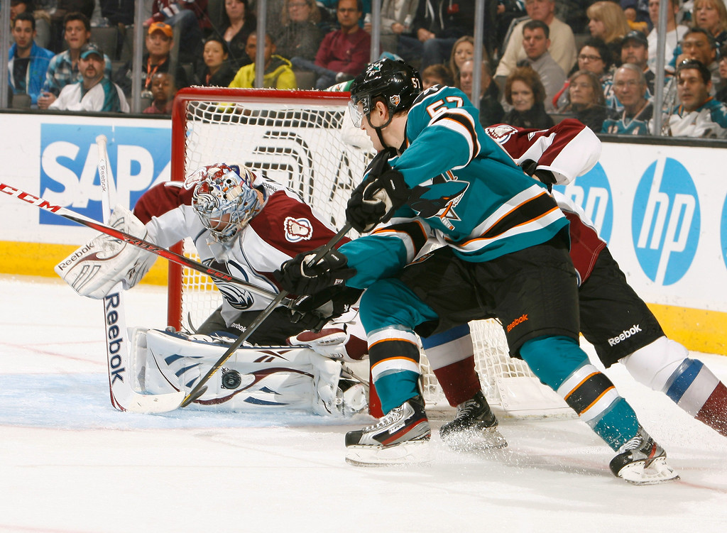 . SAN JOSE, CA - JANUARY 26: Tommy Wingels #57 of the San Jose Sharks crashes the net against Semyon Varlamov #1 of the Colorado Avalanche during an NHL game on January 26, 2013 at HP Pavilion in San Jose, California. (Photo by Don Smith/NHLI via Getty Images)