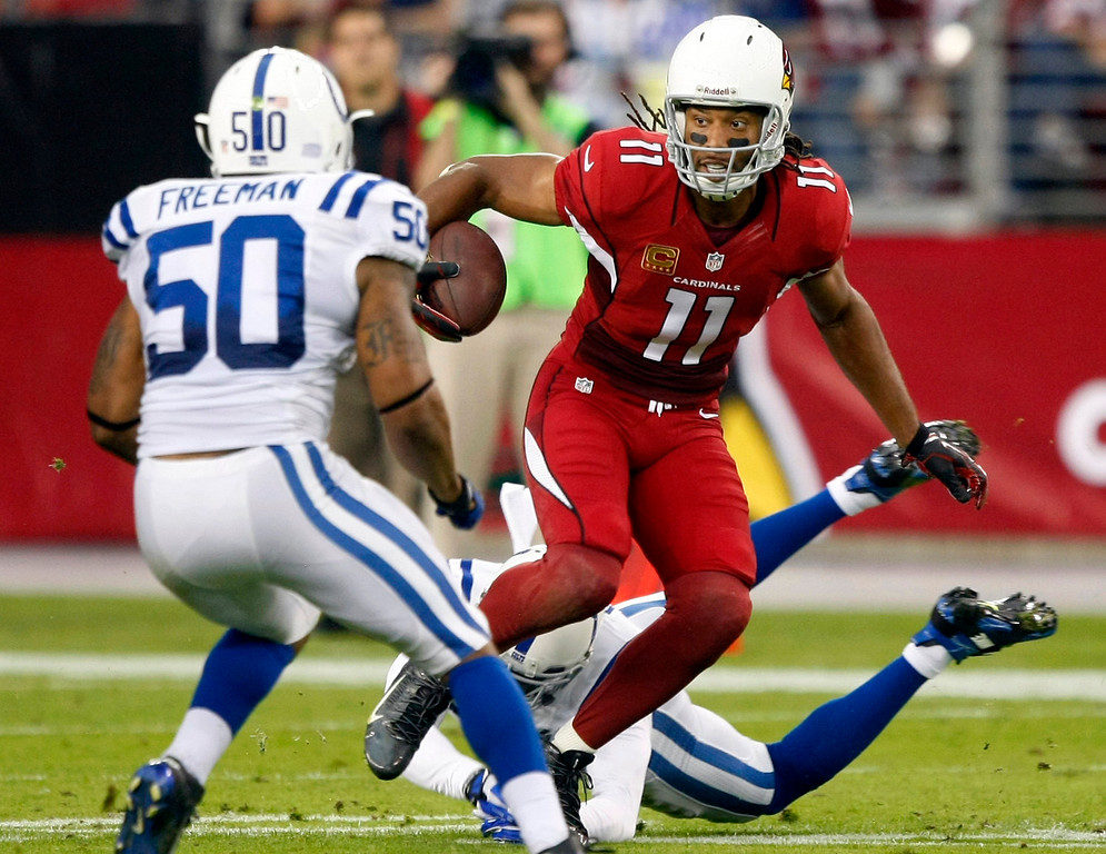 . Arizona Cardinals wide receiver Larry Fitzgerald (11) gains yards after the catch as Indianapolis Colts free safety Darius Butler, rear, and Jerrell Freeman (50) defend during the first half of an NFL football game, Sunday, Nov. 24, 2013, in Glendale, Ariz. (AP Photo/Rick Scuteri)