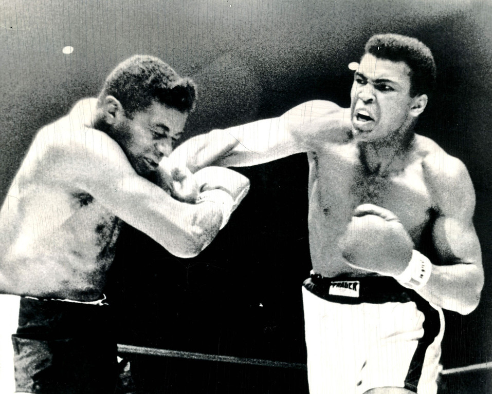 """. CLAY MOVES TOWARD THE KILL--Heavyweight champion Cassius Clay moves in with a series of smashes to the face of challenger Floyd Patterson in the sixth round of their title fight at Las Vegas, Nev., 1965. Clay, suspected by some observers of \""""carrying\"""" Patterson much of the time, turns vicious in the sixth round as he tries to put the challenger away.  Here he smashes a hard right to the face of the grimacing challenger.  Patterson hit deck a moment later. Credit: AP"""