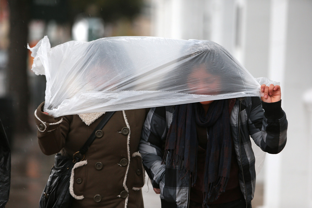 . Two women walk in the freezing rain in downtown Mobile, AL on Tuesday afternoon Jan. 28, 2014. (AP Photo/AL.com, Sharon Steinmann)