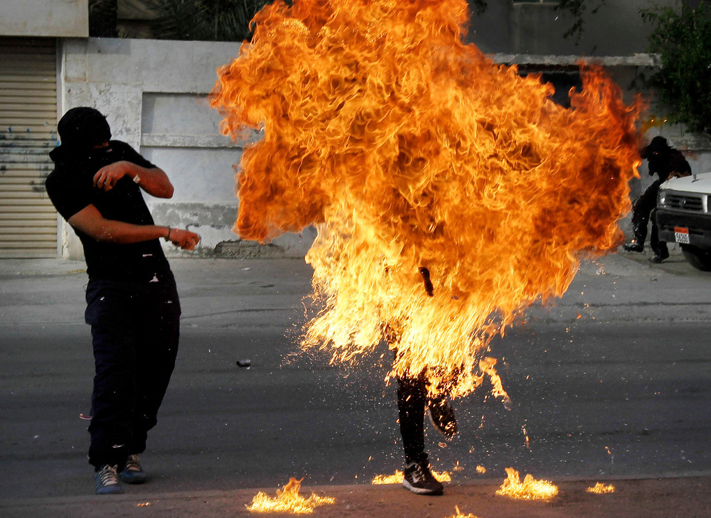 ". A Bahraini anti-government protester is engulfed in flames when a shot fired by riot police hit the petrol bomb in his hand that he was preparing to throw during clashes in Sanabis, Bahrain, Thursday, March 14, 2013. Protests and clashes erupted in opposition areas nationwide with government opponents observing a ""Dignity Strike\"" blocking roads, closing shops, protesting and staying home from work and school called by the more radical February 14 youth group. (AP Photo/Hasan Jamali)"