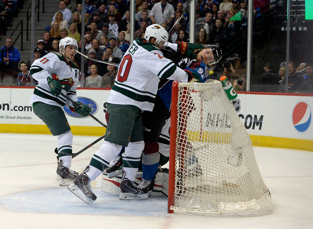 . Ryan Suter (20) of the Minnesota Wild shoves Gabriel Landeskog (92) of the Colorado Avalanche into the net in the Minnesota zone during the first period of action.  (Photo by John Leyba/The Denver Post)