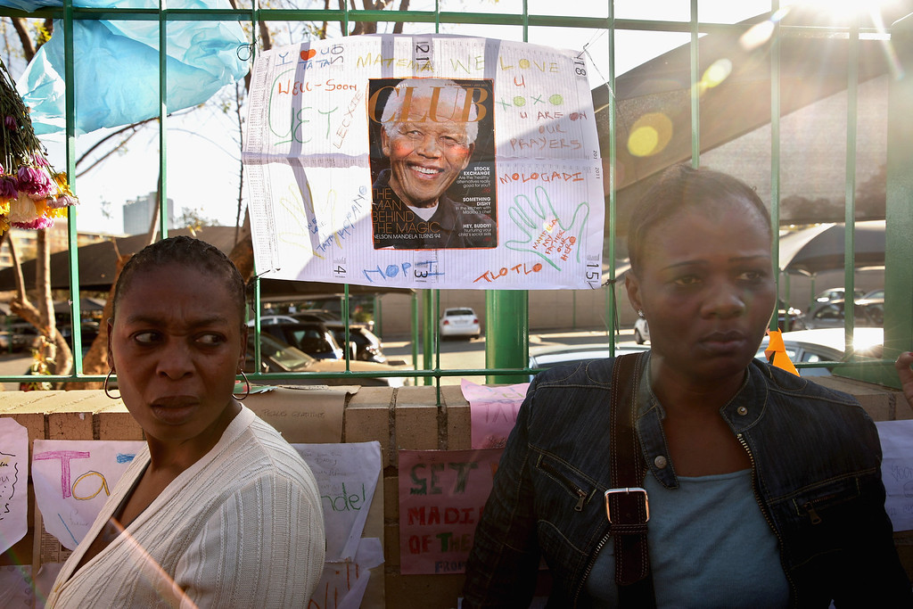 . PRETORIA, SOUTH AFRICA - JUNE 25:  People gather to watch television news reporters outside of the Mediclinic Heart Hospital where former South African President Nelson Mandela is being treated June 25, 2013 in Pretoria, South Africa. South African President Jacob Zuma confirmed on June 23 that Mandela\'s condition has become critical since he was admitted to the hospital over two weeks ago for a recurring lung infection.  (Photo by Chip Somodevilla/Getty Images)