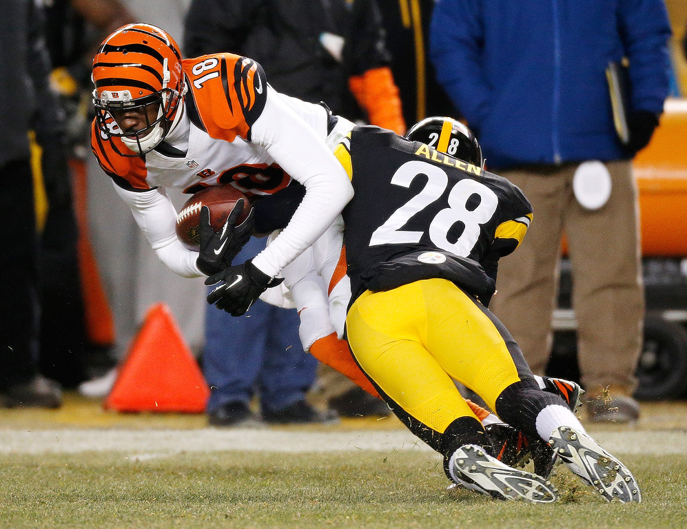 . A.J. Green #18 of the Cincinnati Bengals battles for extra yards after a first quarter catch while being tackled by Cortez Allen #28 of the Pittsburgh Steelers at Heinz Field on December 15, 2013 in Pittsburgh, Pennsylvania.  (Photo by Gregory Shamus/Getty Images)