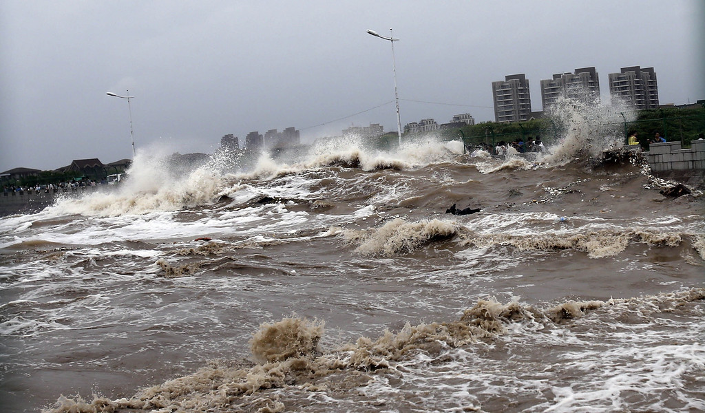". This picture taken on August 22, 2013 shows huge waves from the ""Haining tide\"" - a daily occurrence when the river tides hit the banks of the city - surging higher than usual due to the influence of Typhoon Trami in the region in Haining, in eastern China\'s Zhejiang province. Typhoon Trami, the 12th typhoon to hit China this year, brought rainstorms and wreaked havoc in eastern China after landing in Fujian Province early on August 22.  The tides there have attracted spectators for the past two millennia, and it is the scene of an annual Tide-Watching Festival in late summer.     AFP PHOTOSTR/AFP/Getty Images"