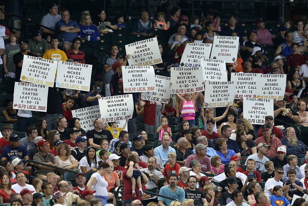. Fans hold up signs to honor the 19 Granite Mountain Interagency Hotshot Crew firefighters who died battling a fast-moving wildfire near Yarnell, AZ during the MLB game between the Arizona Diamondbacks and the Colorado Rockies at Chase Field on July 7, 2013 in Phoenix, Arizona.  (Photo by Christian Petersen/Getty Images)