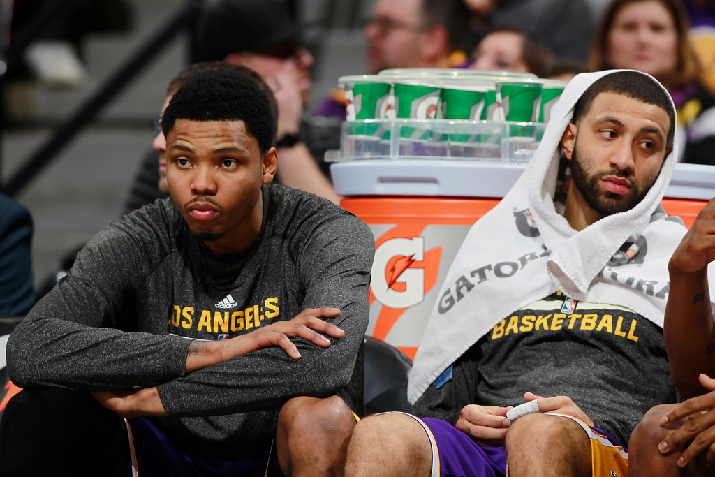 . Los Angeles Lakers guards Kent Bazemore, left, and Kendall Marshall look on from bench as time runs out in the fourth quarter of the Denver Nuggets\' 134-126 victory over the Lakers in an NBA basketball game in Denver on Friday, March 7, 2014. (AP Photo/David Zalubowski)