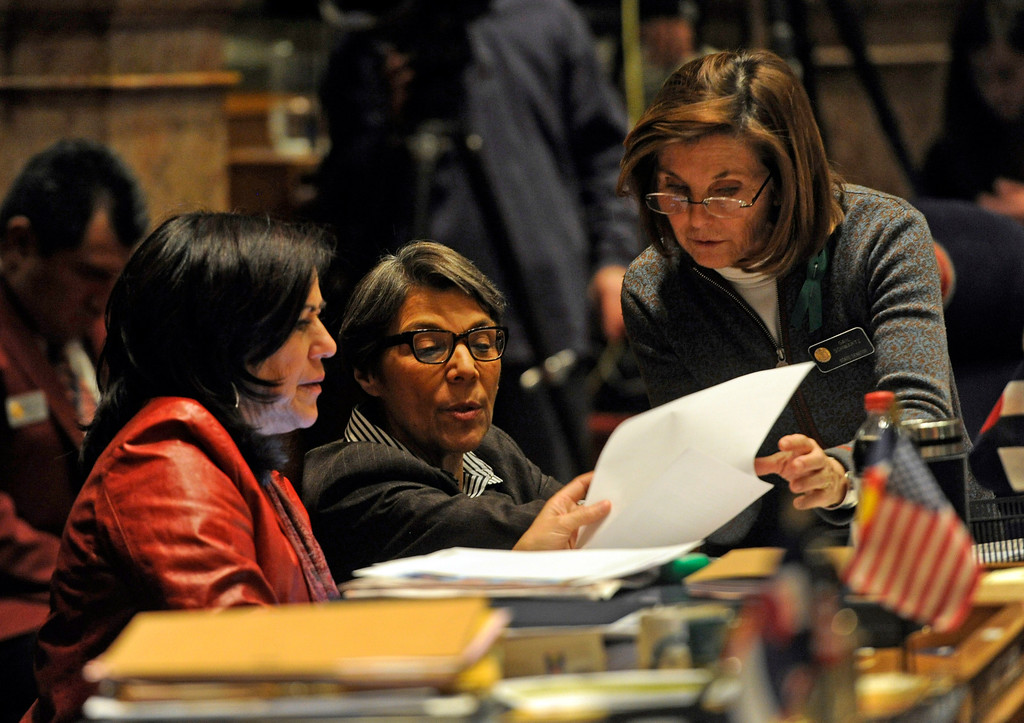 . DENVER, CO. - MARCH 8: Senator Angela Giron, left, Lucia Guzman, and Gail Schwartz, right, meet on the Senate floor. Debate begins on the Senate floor at the state capitol on various gun bills before the state legislature. (Photo By Kathryn Scott Osler/The Denver Post)