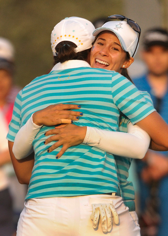 . PARKER, CO. - AUGUST 17: Azahara Munoz embraced teammate Carlota Ciganda after she sunk a putt on the 18th green at the Solheim Cup Saturday. The Spanish golfers took a point away from Americans Gerina Piller and Angela Stanford.  It was the American Team versus the Europeans as play continued at the Colorado Golf Club Saturday afternoon, August 17, 2013. Photo By Karl Gehring/The Denver Post