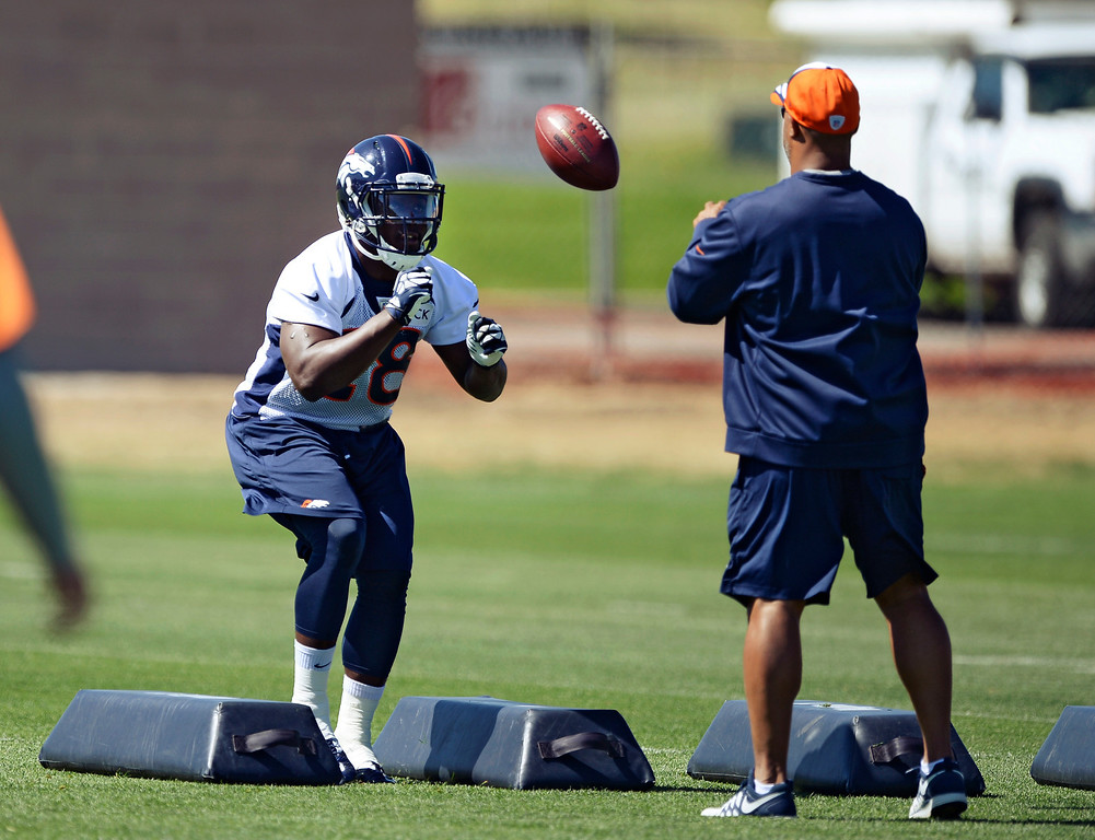 . Denver Broncos running back Montee Ball (28) runs through drills with running backs coach Eric Studesville during OTAs June 2, 2014 at Dove Valley. (Photo by John Leyba/The Denver Post)