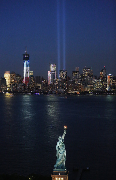. The �Tribute in Light� and Statue of Liberty shine as One World Trade Center (L) rises under construction on the eleventh anniversary of the terrorist attacks on lower Manhattan at the World Trade Center on September 11, 2012 in New York City. New York City and the nation are commemorating the eleventh anniversary of the September 11, 2001 attacks which resulted in the deaths of nearly 3,000 people after two hijacked planes crashed into the World Trade Center, one into the Pentagon in Arlington, Virginia and one crash landed in Shanksville, Pennsylvania. (Photo by Mario Tama/Getty Images)