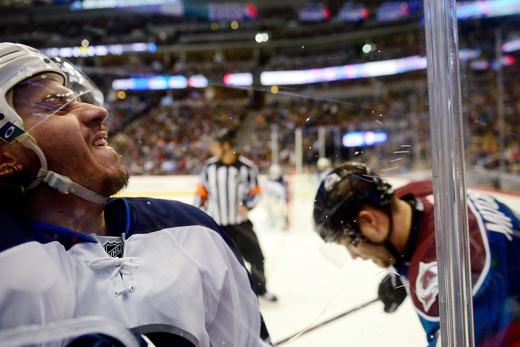 . Keaton Ellerby (7) of the Winnipeg Jets is checked into the glass by Maxime Talbot (25) of the Colorado Avalanche during the first period of action.   (Photo by AAron Ontiveroz/The Denver Post)