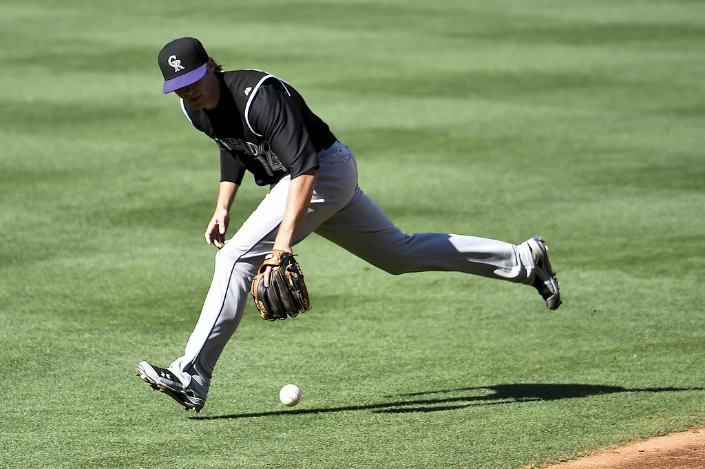 . SAN DIEGO, CA - AUGUST 13:  Josh Rutledge #14 of the Colorado Rockies can\'t make the stop on a single hit by Jedd Gyorko #9 of the San Diego Padres during the third inning of a baseball game at Petco Park on August 13, 2014 in San Diego, California.  (Photo by Denis Poroy/Getty Images)