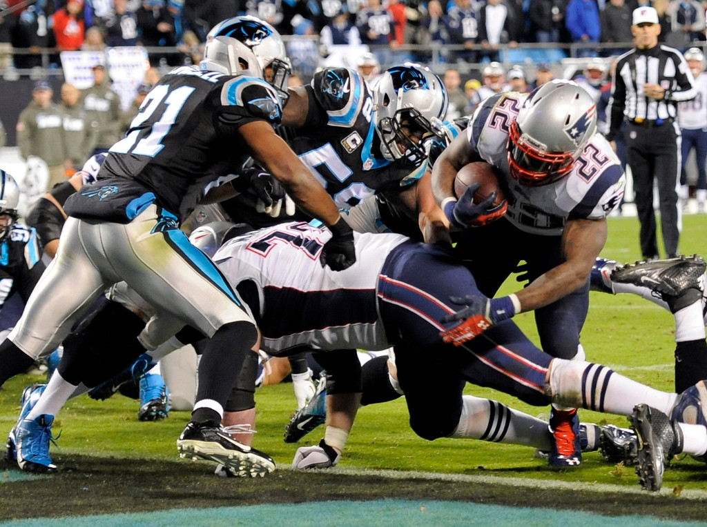 . New England Patriots\' Stevan Ridley (22) runs for a tocuhdown as Carolina Panthers\' Mike Mitchell (21) defends during the second half of an NFL football game in Charlotte, N.C., Monday, Nov. 18, 2013. (AP Photo/Mike McCarn)