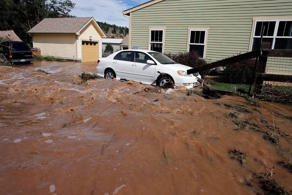 . Water rushes through a neighborhood in Lyons, Colo., Friday Sept. 13, 2013. Days of heavy rains and flash floods which washed out all the town\'s bridges have left Lyons residents stranded from emergency crews, and has sectioned off the town into several pieces not reachable from one to another. (AP Photo/Brennan Linsley)
