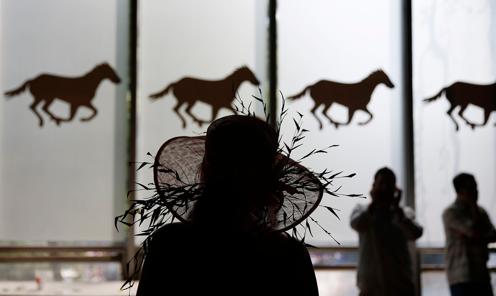 . A woman passes silhouettes of race horses at Belmont Park, Saturday, June 7, 2014, in Elmont, N.Y. The Belmont Stakes will be held at the park later in the day. (AP Photo/Matt Slocum)