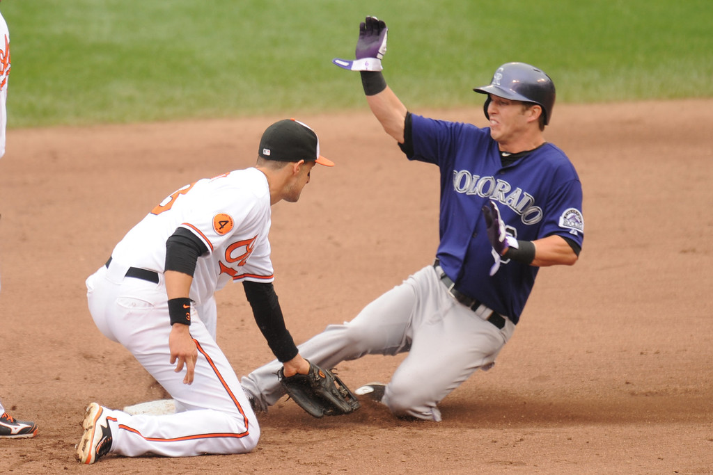 . Corey Dickerson #6 of the Colorado Rockies takes second base on a wild pitch against Ryan Flaherty #3 of the Baltimore Orioles in the sixth inning during a baseball game on August 18, 2013 at Oriole Park at Camden Yards in Baltimore, Maryland.  The Orioles won 7-2.  (Photo by Mitchell Layton/Getty Images)