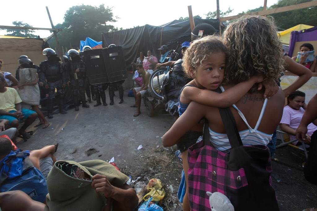 . A woman carries her daughter while standing in front of policemen during an eviction in Rio de Janeiro, Brazil, Friday, April 11, 2014. Squatters in Rio de Janeiro are clashing with police after a Brazilian court ordered that 5,000 people be evicted from abandoned buildings of a telecommunications company. Officers have used tear gas and stun grenades to try to disperse the families. (AP Photo/Silvia Izquierdo)