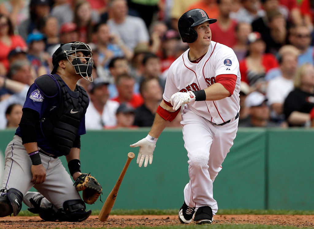 . Boston Red Sox\'s Daniel Nava follows through on a sacrifice fly, driving in a run during the third inning of an interleague baseball game against the Colorado Rockies at Fenway Park in Boston, Wednesday, June 26, 2013. Rockies catcher Yorvit Torrealba watches at left. (AP Photo/Elise Amendola)