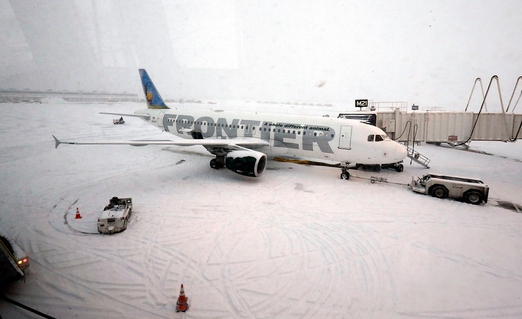. A Frontier airplane waits for passengers at O\'Hare International Airport in Chicago, Thursday, Jan. 2, 2014. Another one to three inches of snow could fall across the Chicago metro area Thursday with even more falling in the southern part of the region, according to the National Weather Service. (AP Photo/Nam Y. Huh)