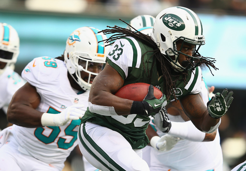 . Chris Ivory #33 of the New York Jets runs with the ball as  Koa Misi #55 of the Miami Dolphins trails during their game at MetLife Stadium on December 1, 2013 in East Rutherford, New Jersey.  (Photo by Al Bello/Getty Images)