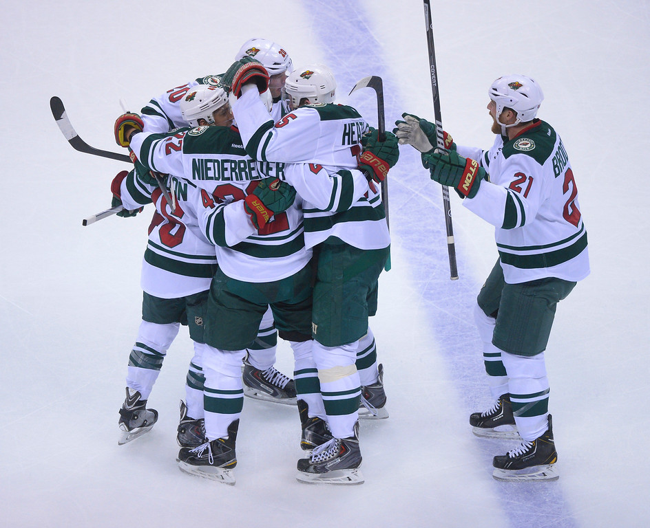 . Wild teammates surrounded defenseman Jared Spurgeon after he tied the game late in the third period to force overtime.   (Photo by Karl Gehring/The Denver Post)