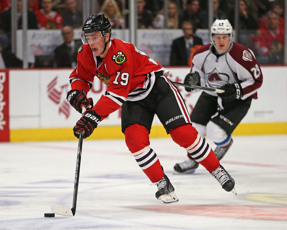 . CHICAGO, IL - DECEMBER 27: Jonathan Toews #19 of the Chicago Blackhawks breaks up the ice past Nathan MacKinnon #29 of the Colorado Avalanche at the United Center on December 27, 2013 in Chicago, Illinois. (Photo by Jonathan Daniel/Getty Images)