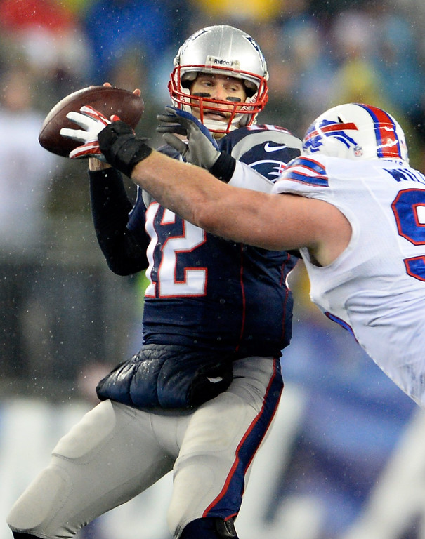 . New England Patriots quarterback Tom Brady (L) makes a pass before the hit from Buffalo Bills defensive tackle Kyle Williams (R) during the first quarter at Gillette Stadium in Foxborough, Massachusetts, USA 29 December 2013.  EPA/CJ GUNTHER