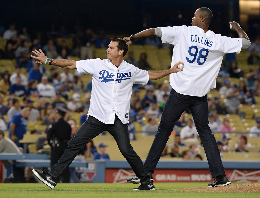 . LOS ANGELES, CA - SEPTEMBER 27:  NBA player Jason Collins and former Major League Baseball player Billy Beane throw out the ceremonial first pitch before the game between the Colorado Rockies and the Los Angeles Dodgers at Dodger Stadium on September 27, 2013 in Los Angeles, California.  (Photo by Harry How/Getty Images)