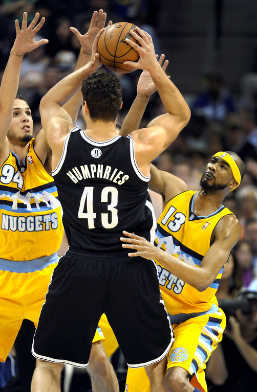 . DENVER, CO. - MARCH 29: Evan Fournier (94) and Corey Brewer (13) of the Denver Nuggets put a double team on Kris Humphries (43) of the Brooklyn Nets in the first half. The Denver Nuggets hosted the Brooklyn Nets Friday night, March 29, 2013 at the Pepsi Center in Denver.  (Photo By Karl Gehring/The Denver Post)