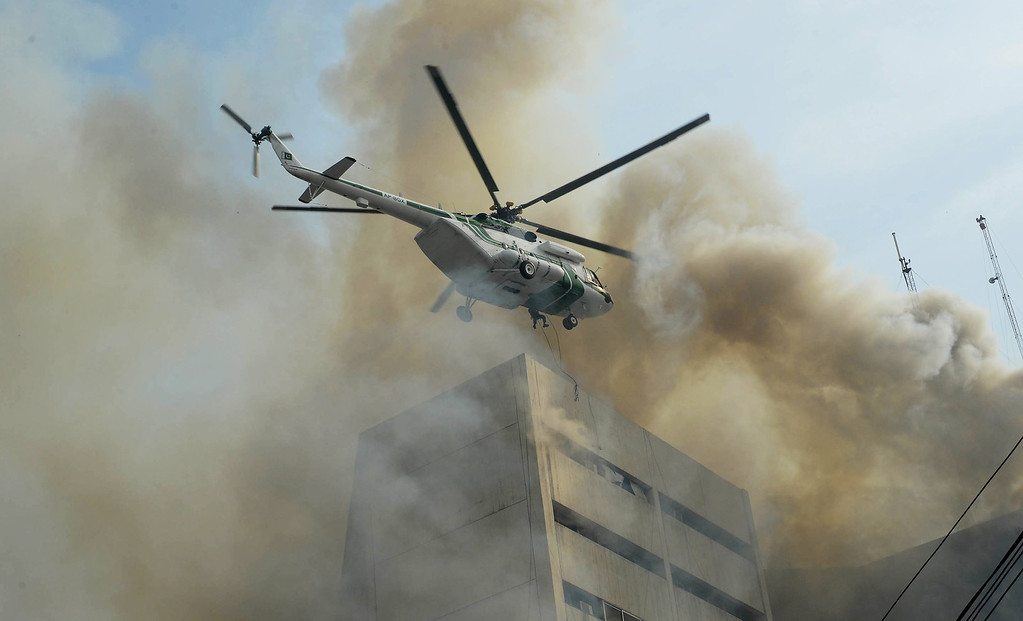 . A Pakistani army helicopter rescues a man from a burning building in Lahore on May 9, 2013.    AFP PHOTO/ Arif Ali/AFP/Getty Images