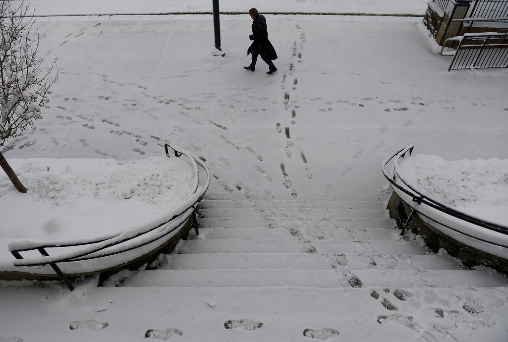 . LITTLETON, CO. - MARCH 23:  A commuter runs for a light rail car at the RTD station in downtown Littleton, CO March 23, 2013. The Saturday forecast calls for snow accumulation of 9 to 12 inches with highs in the lower to mid 20s. (Photo By Craig F. Walker/The Denver Post)