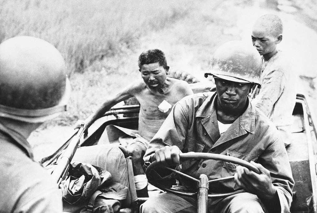 . Cpl. Arthur Warrell, right foreground of New York City, and unidentified 25th Division Buddy, left transport wounded North Koreans on Sept. 1, 1950 whom they captured on the southwestern Korean front to a hospital for treatment. (AP Photo)
